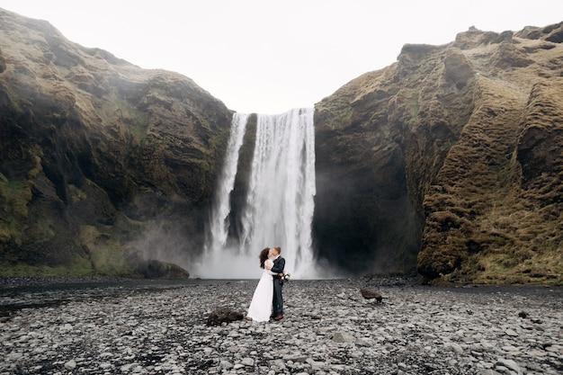 Sposi vicino a skogafoss cascata destinazione islanda matrimonio lo sposo bacia la sposa