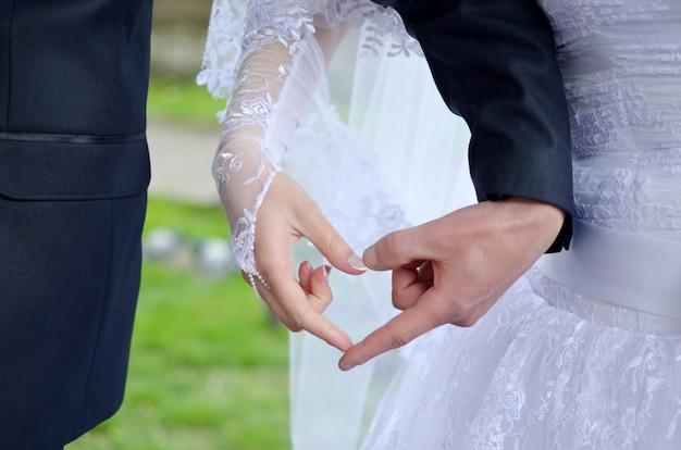 Le mani delle coppie di nozze fanno il cuore