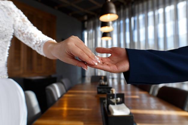 Giorno delle nozze da vicino. coppia innamorata mano nella mano. felice coppia appena sposata. uomo e donna si tengono per mano l'appuntamento romantico nel ristorante. lo sposo raggiunge la sposa