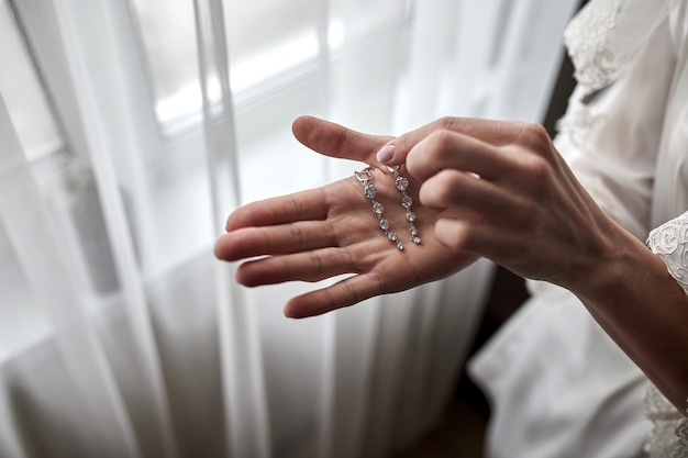 Giorno del matrimonio. primo piano degli orecchini nelle mani della sposa. accessori per gioielli