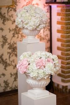 Decorazioni per matrimoni di fiori bianchi e rosa in enormi vasi bianchi
