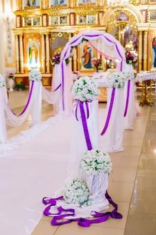 Decorazioni per matrimoni. l'arco è decorato con nastri di tulle e viola con mazzi di rose. cerimonia in chiesa
