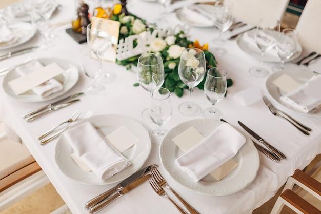 Ricevimento al tavolo della cena di nozze il foglio crema del menu è in un piatto con un tovagliolo di stoffa posate