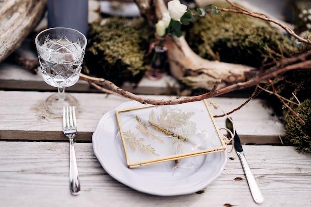 Ricevimento al tavolo della cena di nozze un tavolo improvvisato per due dei pallet da costruzione sull'erba grigia