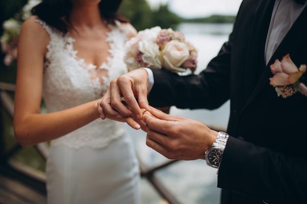 Anelli di fidanzamento di nozze. coppia sposata scambio di fedi nuziali a una cerimonia di matrimonio. lo sposo ha messo un