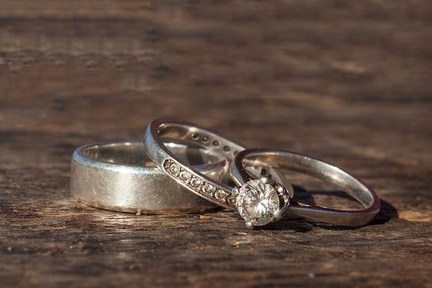 Anelli di fidanzamento e matrimonio su sfondo woden