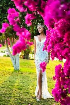 Moda e bellezza per il matrimonio. donna sorridente in abito da sposa bianco in giardino. sposa e cerimonia nuziale. eleganza e modella ragazza in fiore rosa.