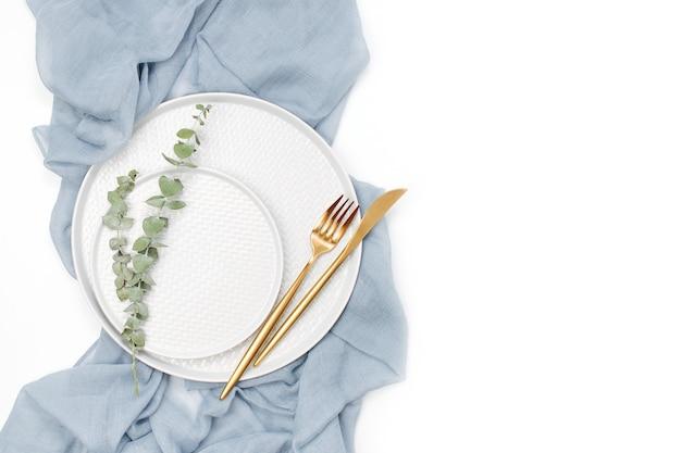 Matrimonio o tavola festiva. piatti e posate con tessuto decorativo grigio su sfondo bianco. bella disposizione.