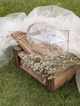 Scatola di vetro per buste per biglietti di auguri su tavolino in legno e tessuto bianco con piante come decorazione