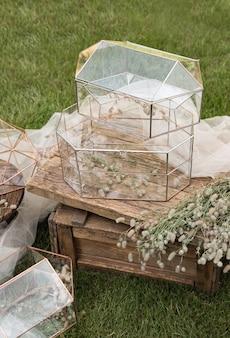 Scatole di vetro per buste per biglietti di auguri di matrimonio su tavolino in legno e tessuto bianco con piante come decorazione