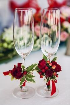 Bicchieri da sposa sul tavolo con decorazioni e fiori
