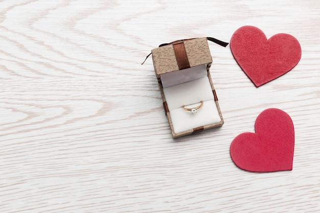 Anello di nozze d'oro in confezione regalo su fondo di legno bianco. san valentino, fidanzamento, anniversario, matrimonio, matrimonio, concetto di amore.
