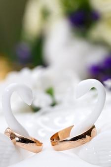 Anelli di nozze d'oro sposi sul cuscino decorativo.