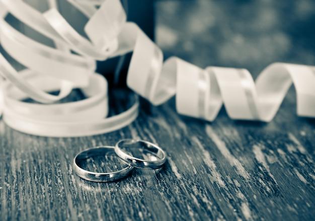 Fedi nuziali d'oro dello sposo e della sposa su un tavolo