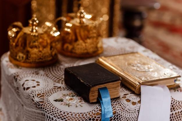 Corone e bibbia dorate di cerimonia nuziale sulla tabella in chiesa. corone di nozze in chiesa pronte per la cerimonia nuziale.