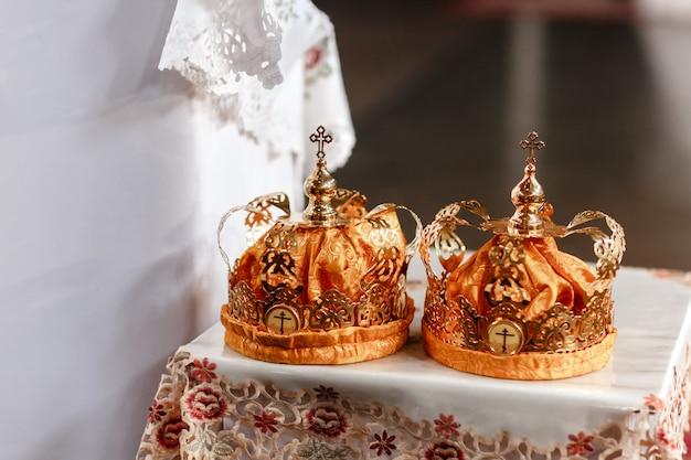 Matrimonio corone d'oro sul tavolo in chiesa. corone di nozze in chiesa pronte per la cerimonia nuziale.