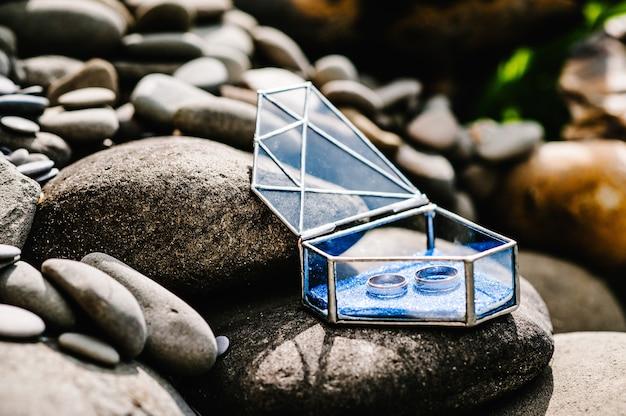 Gli anelli di fidanzamento in argento dorato per matrimoni si trovano in una scatola di metallo a forma di vetro a forma di diamante