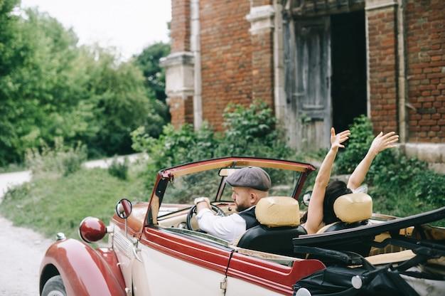 Sposa splendida di nozze e sposo bello in retro automobile vicino alla chiesa