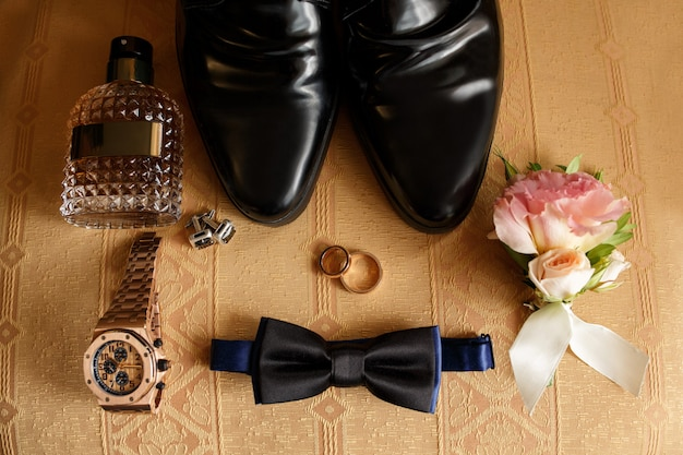 Accessori per lo sposo da sposa su sedia: scarpe nere, orologio da polso, bottiglia di profumo, farfallino vicino alle fedi nuziali