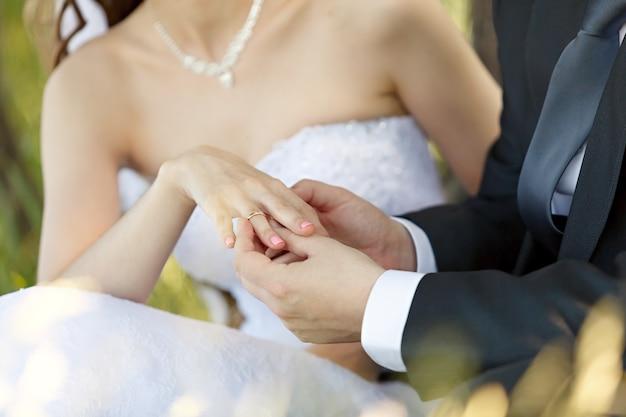 Al matrimonio, lo sposo mette l'anello al dito della sposa. mano dello sposo e della sposa con fedi nuziali a una festa di nozze. all'aperto