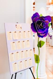 Organizzatore dell'elenco degli invitati di nozze del numero della tabella sul grande fiore artificiale viola della festa nuziale