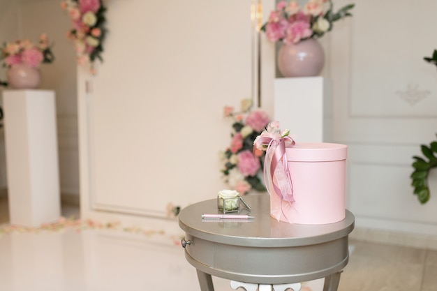 Sala per ricevimenti di matrimonio. un tavolo vicino all'arco di nozze con un salvadanaio per regali agli sposi