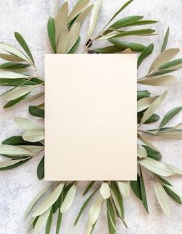 Carta di invito a nozze posata su un tavolo di marmo decorato con rami di ulivo vista dall'alto. elegante modello moderno con carta di carta bianca verticale. modello piatto mediterraneo con posto per il testo