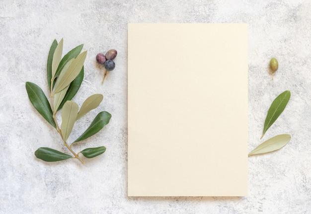 Carta di invito a nozze su un tavolo di marmo decorato con vista dall'alto di rami di ulivo. elegante modello moderno con carta di carta bianca verticale. modello piatto mediterraneo con posto per il testo