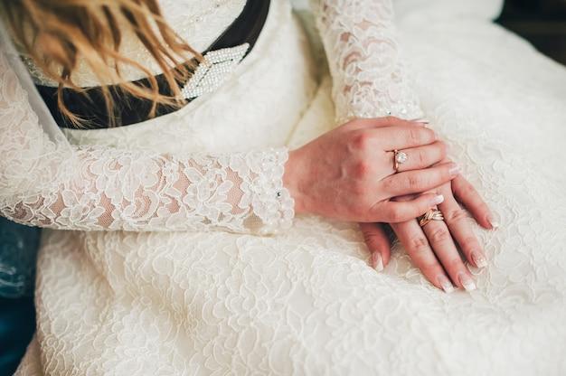 Manicure da sposa da vicino. mani sul vestito. abito bello ed elegante con pizzo francese. braccia con due anelli d'oro. sposa che si siede in un marito in attesa dello sposo.