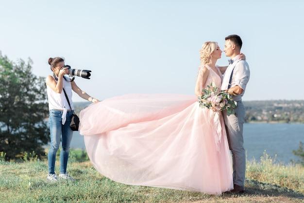 Il fotografo di matrimoni scatta foto della sposa e dello sposo nella natura. sposi sul servizio fotografico. fotografo in azione