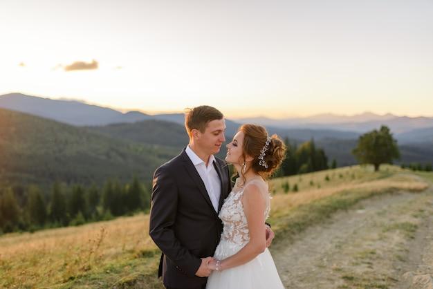 Fotografia di matrimonio in montagna. gli sposi stanno abbracciando. avvicinamento.