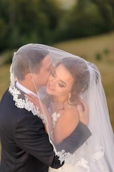 Fotografia di matrimonio in montagna. gli sposi si abbracciano sotto un velo. avvicinamento.