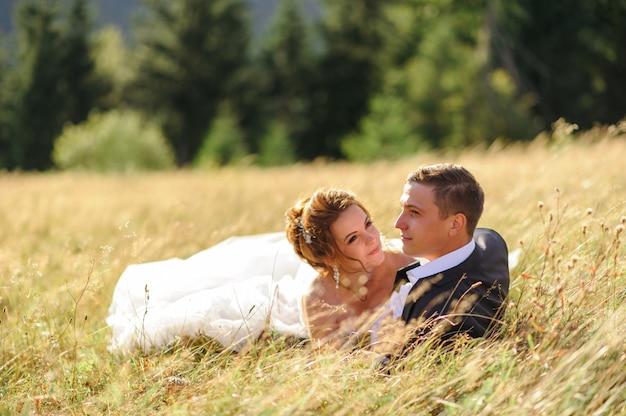 Fotografia di matrimonio in montagna. gli sposi giacciono nell'erba.