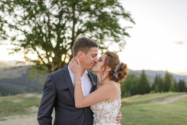 Fotografia di matrimonio in montagna. il bacio degli sposi. avvicinamento.