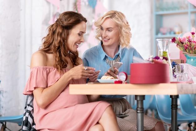 Foto di matrimonio. trasmissione via ir di donna incinta che indossa un elegante abito rosa baggy che mostra le foto del suo matrimonio