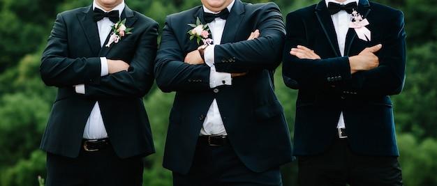 I testimoni e lo sposo del ritratto di nozze stanno sulla natura. giovani amici testimoni dello sposo. amici allegri all'aperto. giorno del matrimonio.