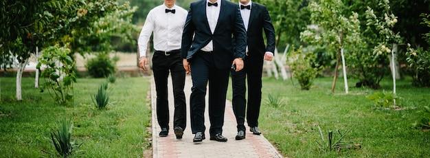 I testimoni e lo sposo del ritratto di matrimonio camminano sulla natura. giovani amici testimoni dello sposo. amici allegri all'aperto. giorno del matrimonio.