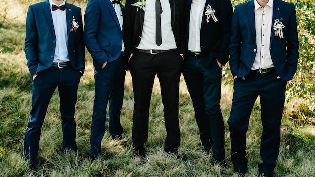 Groomsmen e sposo del ritratto di nozze. giovani amici groomsman in posa. allegri amici all'aperto. giorno del matrimonio.