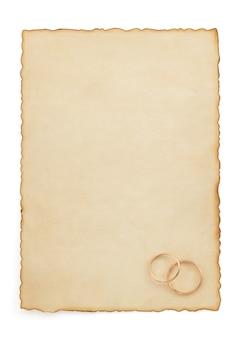 Anello di nozze e carta invecchiata isolata su bianco