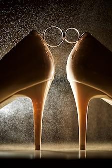 Fede nuziale tra scarpe col tacco alto con schizzi d'acqua