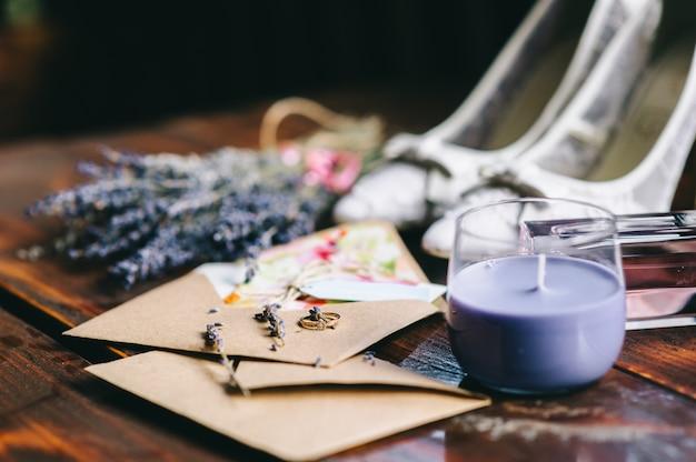 La fede nuziale si trova su una busta artigianale accanto a un bouquet di lavanda, candele e scarpe. dettagli e accessori del matrimonio.