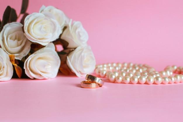 Anello di nozze con rosa bianca sfocata e collana di perle sullo sfondo isolato in rosa