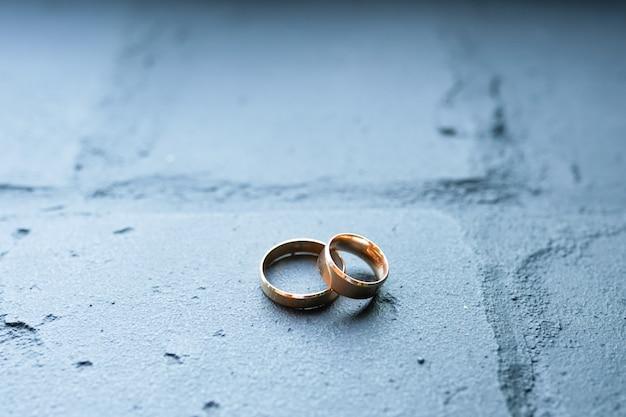 Fedi nuziali sul mattone blu. concetto di anelli d'oro di amore e matrimonio