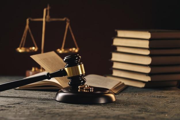 Fedi nuziali sulla figura di un cuore spezzato da un albero, martello di un giudice su uno sfondo di legno. divorzio divorzio