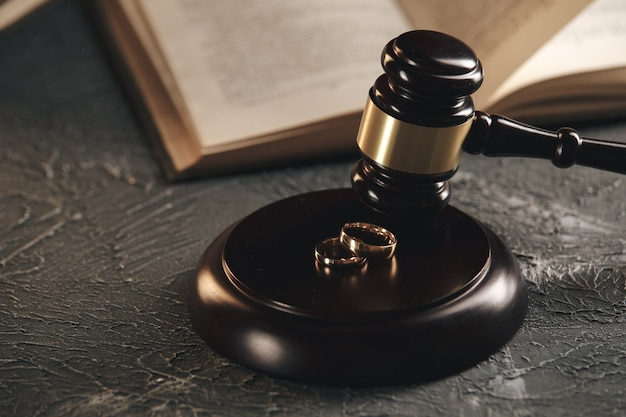 Fedi nuziali sulla figura di un cuore spezzato da un albero, martello di un giudice su uno sfondo di legno. procedimenti di divorzio divorzio