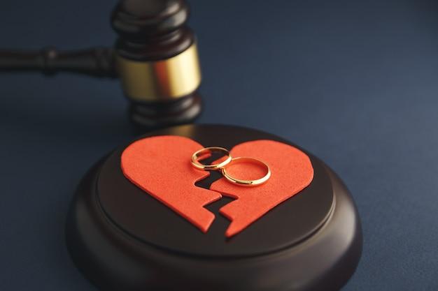 Fedi nuziali sulla figura di un cuore spezzato da un albero, martello di un giudice su uno sfondo di legno. procedimenti di divorzio