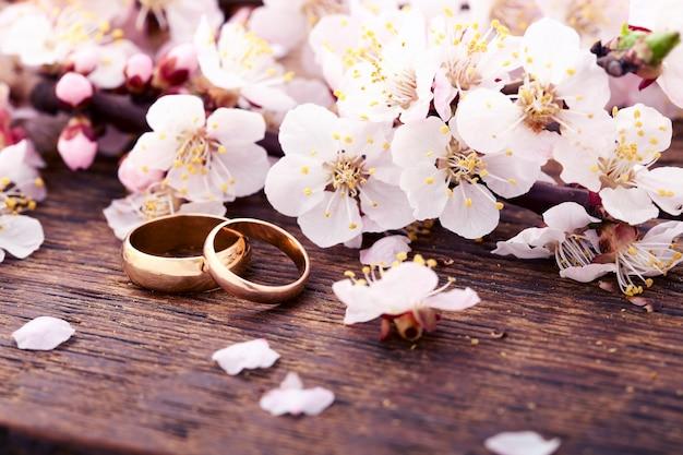 Fedi nuziali e fiori sullo scrittorio di legno.