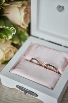 Le fedi nuziali giacciono su una bella scatola con fiori come accessori da sposa