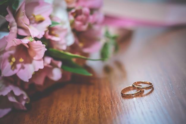 Gli anelli di nozze si trovano su una superficie di legno