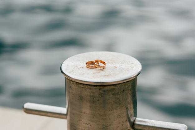Fedi nuziali degli sposi vicino al mare anelli di fidanzamento in oro
